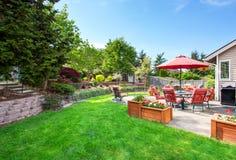 Καλά κρατημένος κήπος στο κατώφλι με τη συγκεκριμένη περιοχή patio πατωμάτων στοκ φωτογραφία με δικαίωμα ελεύθερης χρήσης