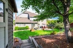 Καλά κρατημένος κήπος στο κατώφλι με τη συγκεκριμένη περιοχή patio πατωμάτων στοκ εικόνες