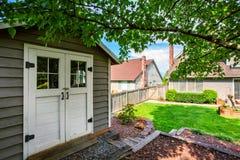 Καλά κρατημένος κήπος στο κατώφλι με το υπόστεγο σιταποθηκών στοκ εικόνα