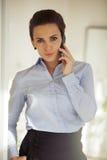 Καλά ντυμένη επιχειρηματίας που μιλά στο τηλέφωνο Στοκ Εικόνες