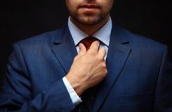 Καλά ντυμένος επιχειρηματίας που ρυθμίζει το δεσμό λαιμών του Στοκ Εικόνες