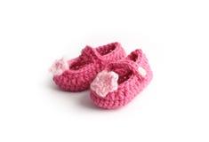 Καλά χειροποίητα χαριτωμένα κόκκινα παπούτσια μωρών το ρόδινο λουλούδι που γίνεται με από το μαλλί Στοκ Φωτογραφία