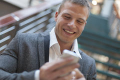 Καλές ειδήσεις! Άτομα που διαβάζουν sms στο smartphone στο επιχειρησιακό κτήριο Στοκ φωτογραφίες με δικαίωμα ελεύθερης χρήσης