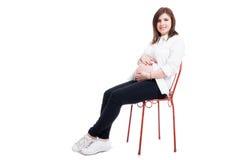 Καλή έγκυος γυναίκα που κάθεται και που χαϊδεύει την κοιλιά της Στοκ Εικόνες