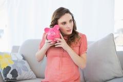 Καλή έγκυος γυναίκα που τινάζει μια piggy συνεδρίαση τραπεζών στον καναπέ Στοκ Εικόνες