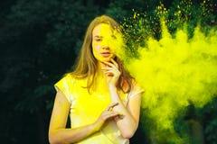 Καλή γυναίκα brunette με τη σκόνη Holi που εκρήγνυται γύρω από την Στοκ Εικόνες
