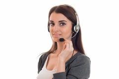 Καλή γυναίκα brunette που λειτουργούν στο τηλεφωνικό κέντρο με τα ακουστικά και μικρόφωνο που εξετάζει τη κάμερα και το χαμόγελο  Στοκ Φωτογραφία