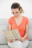 Καλή γυναίκα brunette που διαβάζει μια συνεδρίαση περιοδικών στον καναπέ Στοκ Φωτογραφία