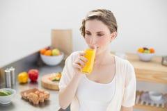 Καλή γυναίκα brunette που πίνει ένα ποτήρι του χυμού από πορτοκάλι που στέκεται στην κουζίνα της Στοκ Εικόνες