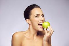 Καλή γυναίκα brunette που τρώει το φρέσκο πράσινο μήλο Στοκ Εικόνες