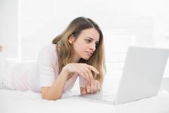 Καλή γυναίκα brunette που χρησιμοποιεί το σημειωματάριό της που βρίσκεται στο κρεβάτι της Στοκ φωτογραφίες με δικαίωμα ελεύθερης χρήσης