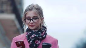 Καλή νέα γυναίκα που πίνει ένα φλυτζάνι του καυτού καφέ και που χρησιμοποιεί το τηλέφωνο κυττάρων της για απασχολημένος τρόπος ζω απόθεμα βίντεο