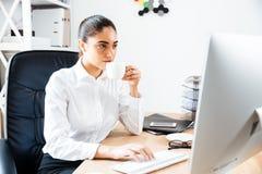 Καλή νέα επιχειρηματίας χρησιμοποιώντας το lap-top και πίνοντας το φλιτζάνι του καφέ Στοκ Εικόνα
