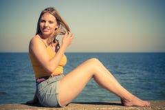 Καλή ξανθή χαλάρωση κοριτσιών υπαίθρια από την παραλία Στοκ εικόνες με δικαίωμα ελεύθερης χρήσης