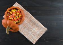 Καλαμπόκι καραμελών στην κεραμική κολοκύθα με την πετσέτα Στοκ Φωτογραφία