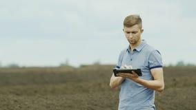 καλλιέργεια οργανική Ένας νέος αγρότης εργάζεται κοντά στους σωρούς του λιπάσματος ή το λίπασμα, χρησιμοποιεί μια ταμπλέτα φιλμ μικρού μήκους