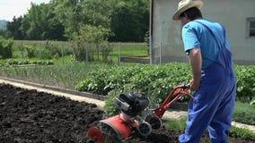 Καλλιέργεια του κήπου με το smal καλλιεργητή σε σε αργή κίνηση φιλμ μικρού μήκους