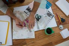 Καλλιεργημένα χέρια της γραμμής σχεδίων σχεδιαστών σε χαρτί στην αρχή Στοκ Φωτογραφία