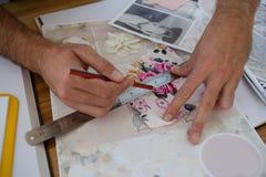 Καλλιεργημένα χέρια της γραμμής σχεδίων σχεδιαστών σε χαρτί στον πίνακα Στοκ Εικόνες