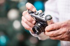 Καλλιεργημένη άποψη του ατόμου που κρατά την αναδρομική κάμερα Στοκ Φωτογραφίες