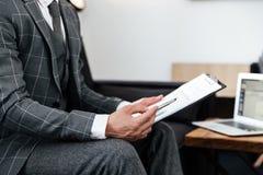 Καλλιεργημένη εικόνα ενός ατόμου στο κοστούμι που αναλύει τα έγγραφα Στοκ Εικόνες