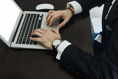 Καλλιεργημένη εικόνα ενός νεαρού άνδρα που εργάζεται στο lap-top του οπισθοσκόπο του πολυάσχολου χρησιμοποιώντας lap-top χεριών ε Στοκ Φωτογραφίες