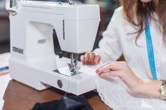 Καλλιεργημένη εικόνα του θηλυκού ράφτη που ράβει τη λεπτή δαντέλλα με τη συνεδρίαση μηχανών ραψίματος dressmaking στο στούντιο Στοκ Φωτογραφία