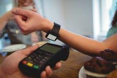 Καλλιεργημένη εικόνα του πελάτη με το έξυπνο ρολόι στον καφέ Στοκ εικόνα με δικαίωμα ελεύθερης χρήσης