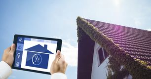 Καλλιεργημένη εικόνα του προσώπου που χρησιμοποιεί το έξυπνο σπίτι app με το σπίτι στο υπόβαθρο Στοκ Εικόνες