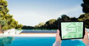 Καλλιεργημένη εικόνα του προσώπου που χρησιμοποιεί το έξυπνο σπίτι app στο PC ταμπλετών στο poolside Στοκ εικόνα με δικαίωμα ελεύθερης χρήσης