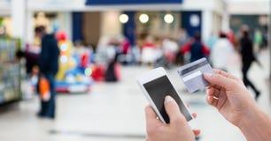 Καλλιεργημένη εικόνα του προσώπου που χρησιμοποιεί το έξυπνο τηλέφωνο για την πληρωμή του λογαριασμού μέσω της χρεωστικής κάρτας στοκ εικόνα