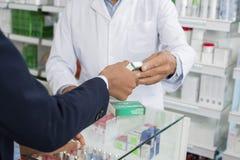 Καλλιεργημένη εικόνα του φαρμακοποιού που δίνει την ιατρική στο θηλυκό πελάτη στοκ φωτογραφία με δικαίωμα ελεύθερης χρήσης