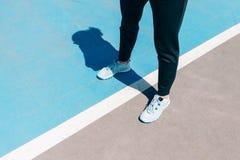 Καλλιεργημένη εικόνα των θηλυκών ποδιών στα πάνινα παπούτσια και μαύρο standin εσωρούχων στοκ εικόνες