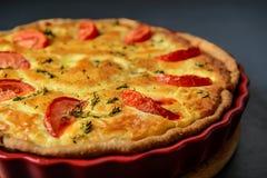 Καλλιεργημένη κινηματογράφηση σε πρώτο πλάνο φωτογραφία της κλασικής πίτας της Λωρραίνης πίτα με το tomat στοκ φωτογραφία