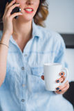 Καλλιεργημένη πυροβοληθείσα άποψη της νέας ομιλίας γυναικών σε ένα τηλέφωνο κυττάρων με το φλυτζάνι στο χέρι της Στοκ Εικόνες