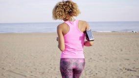 Καλλιεργημένος οπισθοσκόπος του τρεξίματος γυναικών στην παραλία φιλμ μικρού μήκους