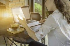 Καλλιεργημένος πυροβολισμός της γυναίκας στον καφέ που λειτουργεί στο φορητό προσωπικό υπολογιστή της και Στοκ Φωτογραφίες