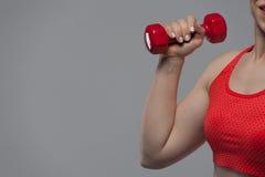 Καλλιεργημένος πυροβολισμός της κατάλληλης γυναίκας που ανυψώνει τον κόκκινο αλτήρα Στοκ φωτογραφία με δικαίωμα ελεύθερης χρήσης