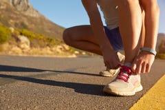 Καλλιεργημένος πυροβολισμός του θηλυκού jogger που κάνει επάνω τη δαντέλλα παπουτσιών της Στοκ εικόνες με δικαίωμα ελεύθερης χρήσης