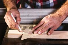 Καλλιεργημένο χέρι ενός ξυλουργού που παίρνει τη μέτρηση μιας ξύλινης σανίδας στοκ φωτογραφία με δικαίωμα ελεύθερης χρήσης