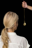 Καλλιεργημένο χέρι του εκκρεμούς εκμετάλλευσης hypnotherapist από τη γυναίκα Στοκ Εικόνες