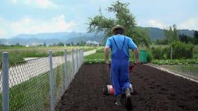 Καλλιεργητής που περπατά πίσω από τον οργώνοντας καλλιεργητή φιλμ μικρού μήκους