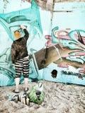 Καλλιτέχνης γκράφιτι που χρωματίζει την παλαιά αποθήκη Στοκ Εικόνες