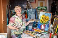 Καλλιτέχνης γυναικών κοντά στην εικόνα ελαιογραφίας στο στούντιο Στοκ εικόνα με δικαίωμα ελεύθερης χρήσης