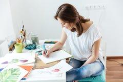 Καλλιτέχνης γυναικών που κάνει τα σκίτσα στο εργαστήριο Στοκ φωτογραφία με δικαίωμα ελεύθερης χρήσης