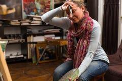 Καλλιτέχνης γυναικών που σταματά για να σκουπίζει το μέτωπό της στοκ εικόνες