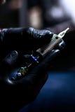 Καλλιτέχνης δερματοστιξιών που κάνουν τη δερματοστιξία Κύριες εργασίες για την επαγγελματική μηχανή και στα αποστειρωμένα μαύρα γ Στοκ Φωτογραφίες