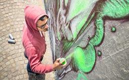 Καλλιτέχνης οδών που χρωματίζει τα ζωηρόχρωμα γκράφιτι στο γενικό τοίχο Στοκ εικόνες με δικαίωμα ελεύθερης χρήσης