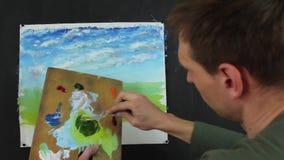 Καλλιτέχνης που εργάζεται σε μια ζωγραφική Ελαιογραφία χρωμάτων καλλιτεχνών στον καμβά απόθεμα βίντεο