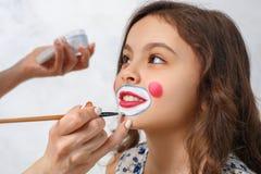 Καλλιτέχνης που κάνει τον κλόουν makeup για ένα μικρό κορίτσι Στοκ εικόνα με δικαίωμα ελεύθερης χρήσης